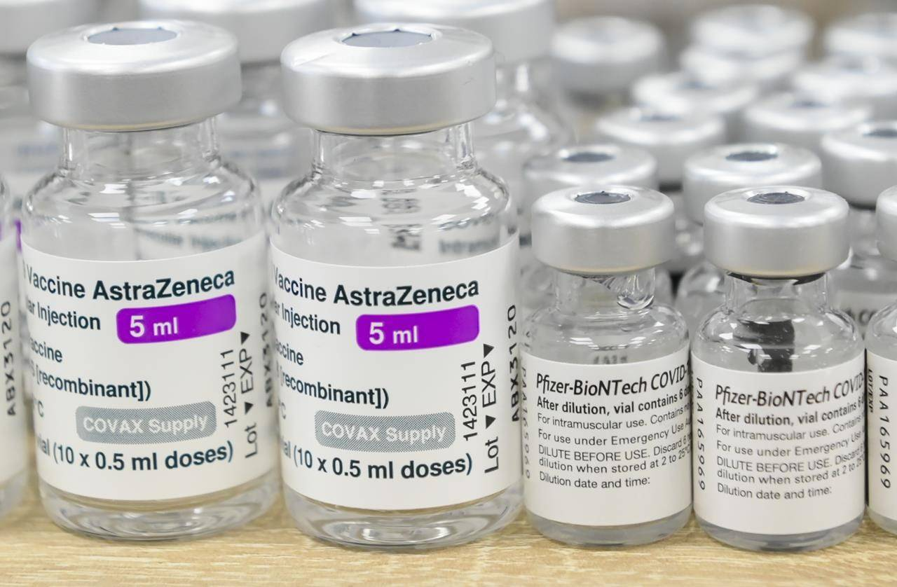 Vials of both Pfizer-BioNTech and Oxford-AstraZeneca COVID-19 vaccines sit empty on the counter at the Junction Chemist Pharmacy, in Toronto, Friday, June 18, 2021. Health Canada reports that at least 1.3 million Canadians opted for a mixed-dose finish to their COVID-19 vaccination schedule in June. THE CANADIAN PRESS/Nathan Denette