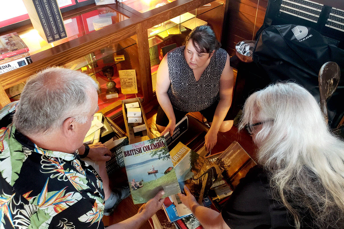 Kurt Langmann, AGHS vice-president Brenda Haid, and Tami Quiring looking at some of the Beautiful British Columbia issues included in a recent donation. (Scott White/Special to The Star)