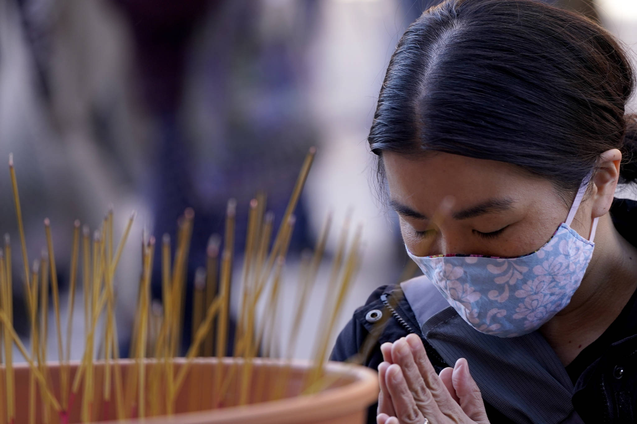 A woman prays in front of incense sticks to honor the victims of the Atlanta area massage parlor shootings during a memorial in Kansas City, Mo., Sunday, March 28, 2021. The March 17 shootings at three Georgia massage parlors and spas that left eight people dead, six of them women of Asian descent, come on the heels of a recent wave of attacks against Asian Americans since the coronavirus entered the United States. (AP Photo/Charlie Riedel)