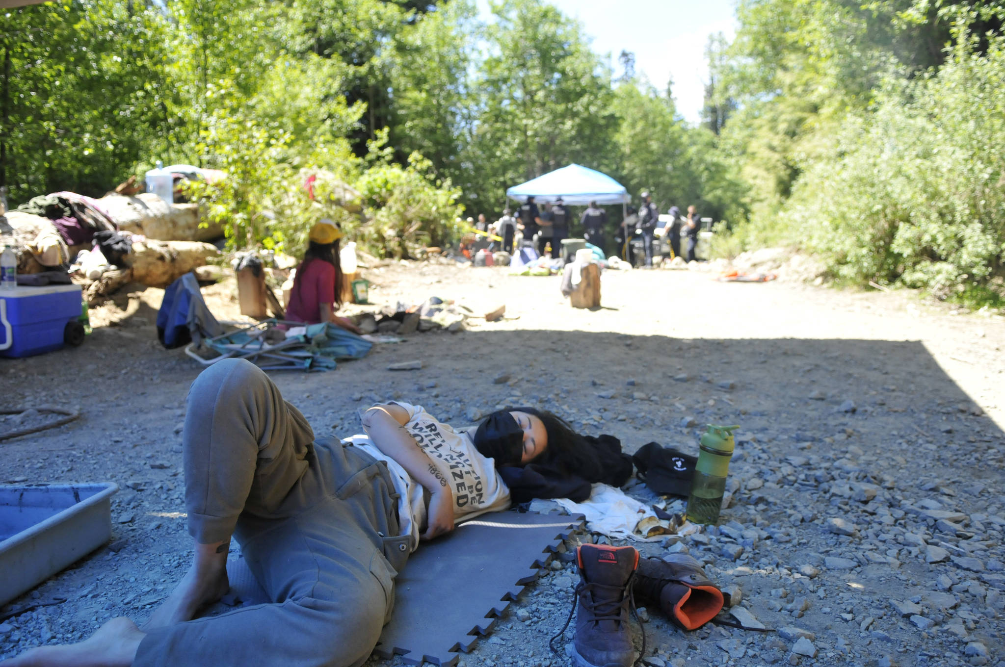 A protester lies in a sleeping dragon hold at the Waterfall blockade in June in the Fairy Creek Watershed, while police confer in the background. (Zoe Ducklow/News Staff)