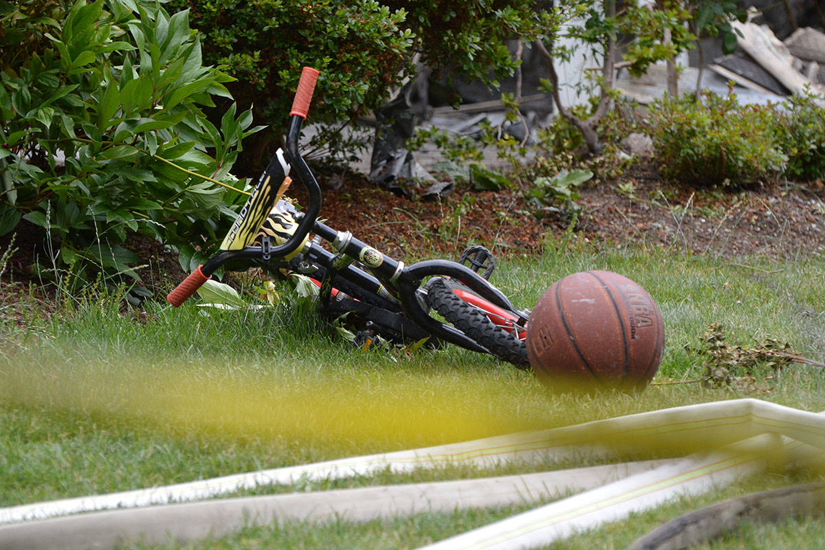 A child-sized bicycle and basketball rest behind police tape after a house fire in Surrey. Police are investigating after a five-year-old child was found dead. (Aaron Hinks photo)