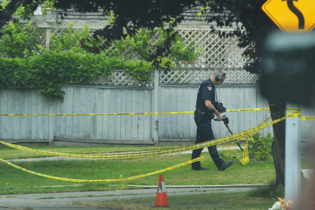A police officer uses a metal detector at the scene of a Surrey house fire Wednesday afternoon. (Aaron Hinks photo)