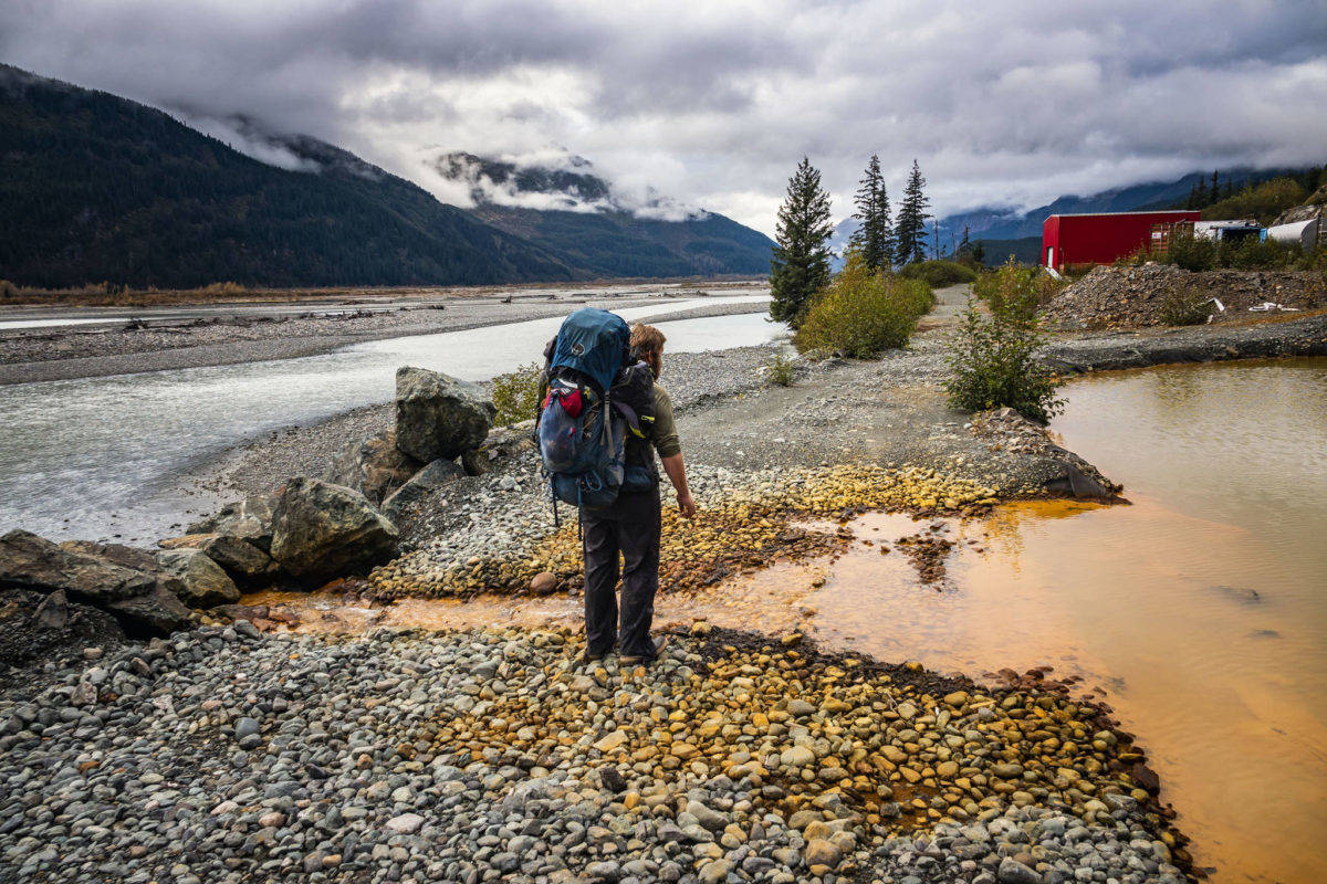 Bjorn Dihle inspects the acid mine drainage flowing into the Tulsequah River from a containment pond filled by effluent from the Tulsequah Chief Mine in B.C., October 2018. The mine cleanup has been a point of dispute between B.C. and Alaska for many years. (Chris Miller photo)