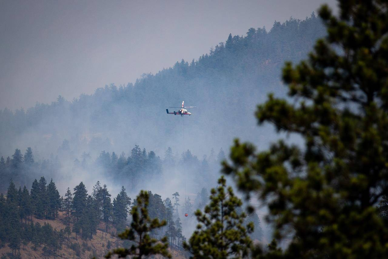 A helicopter pilot prepares to drop water on a wildfire burning in Lytton, B.C., on Friday, July 2, 2021. (THE CANADIAN PRESS/Darryl Dyck)