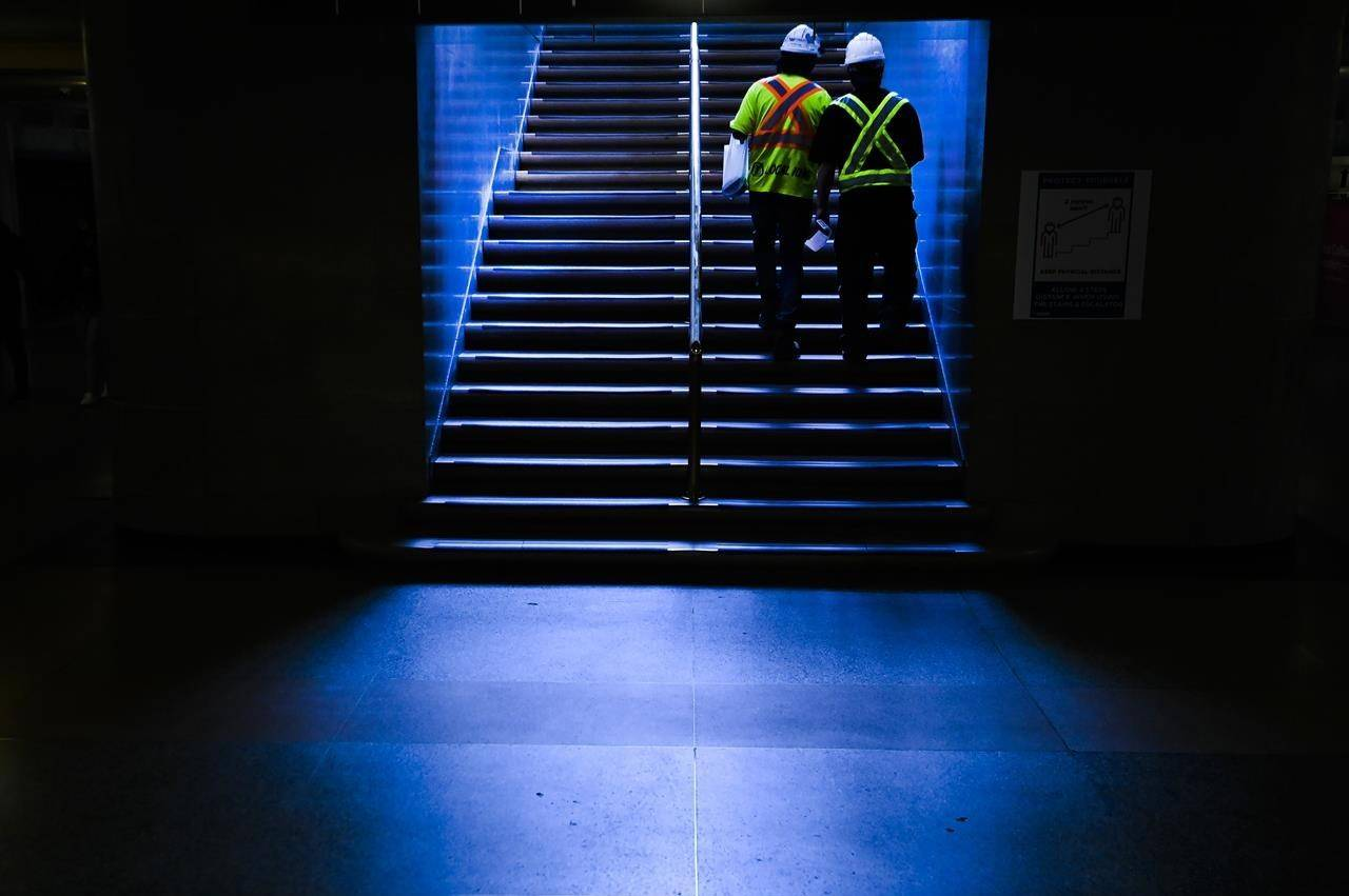 Construction workers walk up a set of stairs at Union Station during the COVID-19 pandemic in Toronto on Tuesday, May 11, 2021. THE CANADIAN PRESS/Nathan Denette