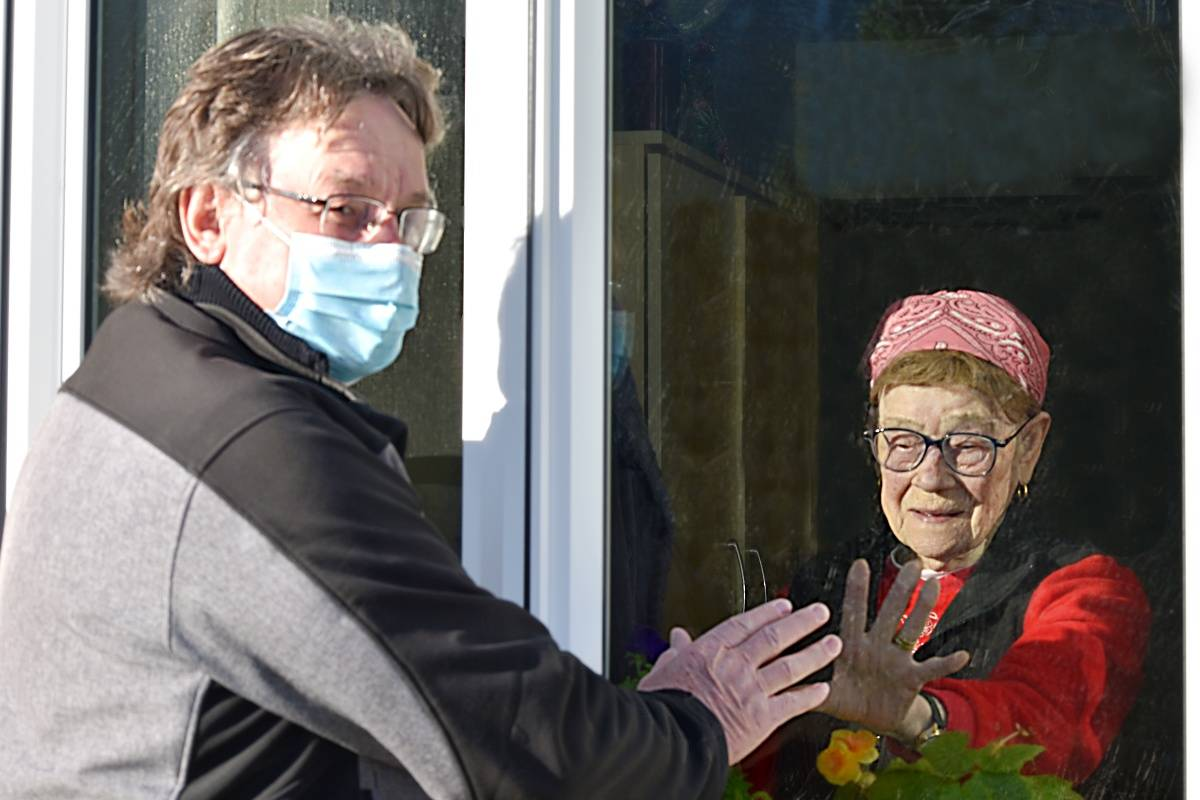 Rose Sawka, 91, reaches out to her son Terry Sawka, on a daily visit through the window at a Prince Rupert senior care home in early 2021. (Photo: K-J Millar/The Northern View)