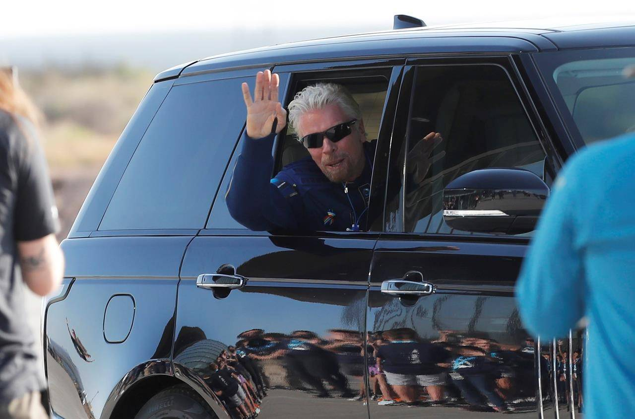Virgin Galactic founder Richard Branson waves good bye while heading to board the rocket plane that will fly him to space from Spaceport America near Truth or Consequences, New Mexico, Sunday, July 11, 2021. (AP Photo/Andres Leighton)