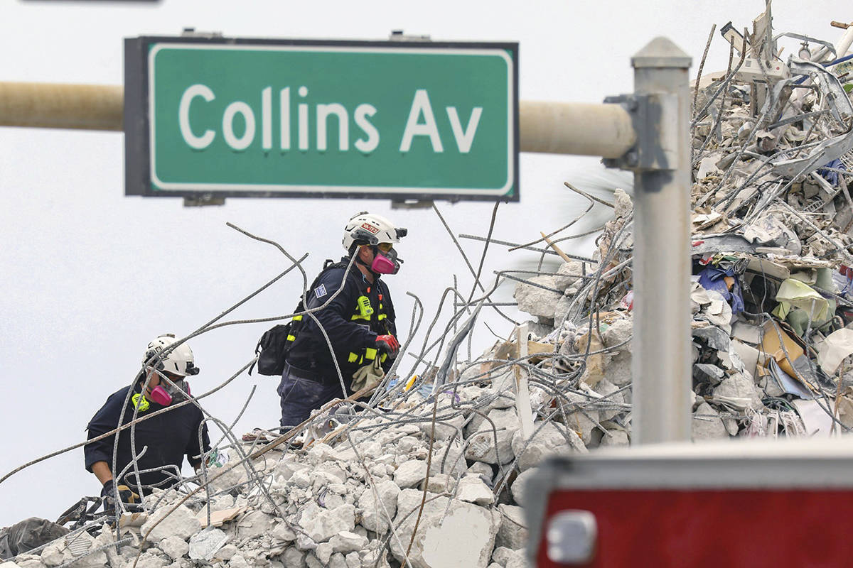 Search and rescue team members climb the debris field of the 12-story oceanfront condo, Champlain Towers South along Collins Avenue in Surfside, Fla., on Wednesday, July 7, 2021. (Al Diaz/Miami Herald via AP)