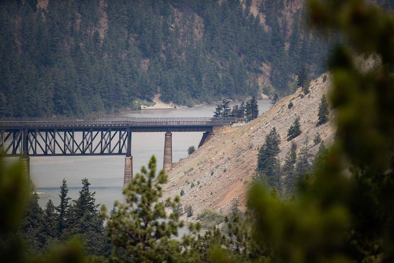 A rail bridge spans the Fraser River as a wildfire burns in Lytton, B.C., on Friday, July 2, 2021. THE CANADIAN PRESS/Darryl Dyck