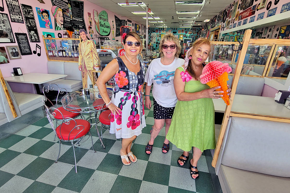 Shannon Brogan is book-ended by singers Deborah Owen (L) and Pinky Cholette on Saturday, July 10, as 60 vehicles took part in the annual cancer fundraiser organized by the Old Fart Car Club and Brogan's Diner in Langley City. (Dan Ferguson/Langley Advance Times)
