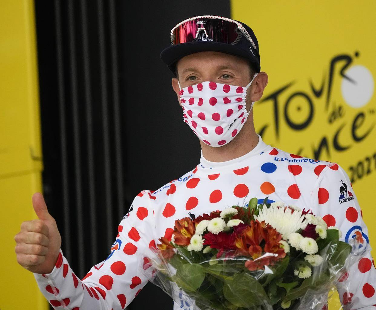 Michael Woods of Canada, wearing the best climber's dotted jersey, celebrates on the podium after the fourteenth stage of the Tour de France cycling race over 183.7 kilometers (114.1 miles) with start in Carcassonne and finish in Quillan, France, Saturday, July 10, 2021. (AP Photo/Christophe Ena)