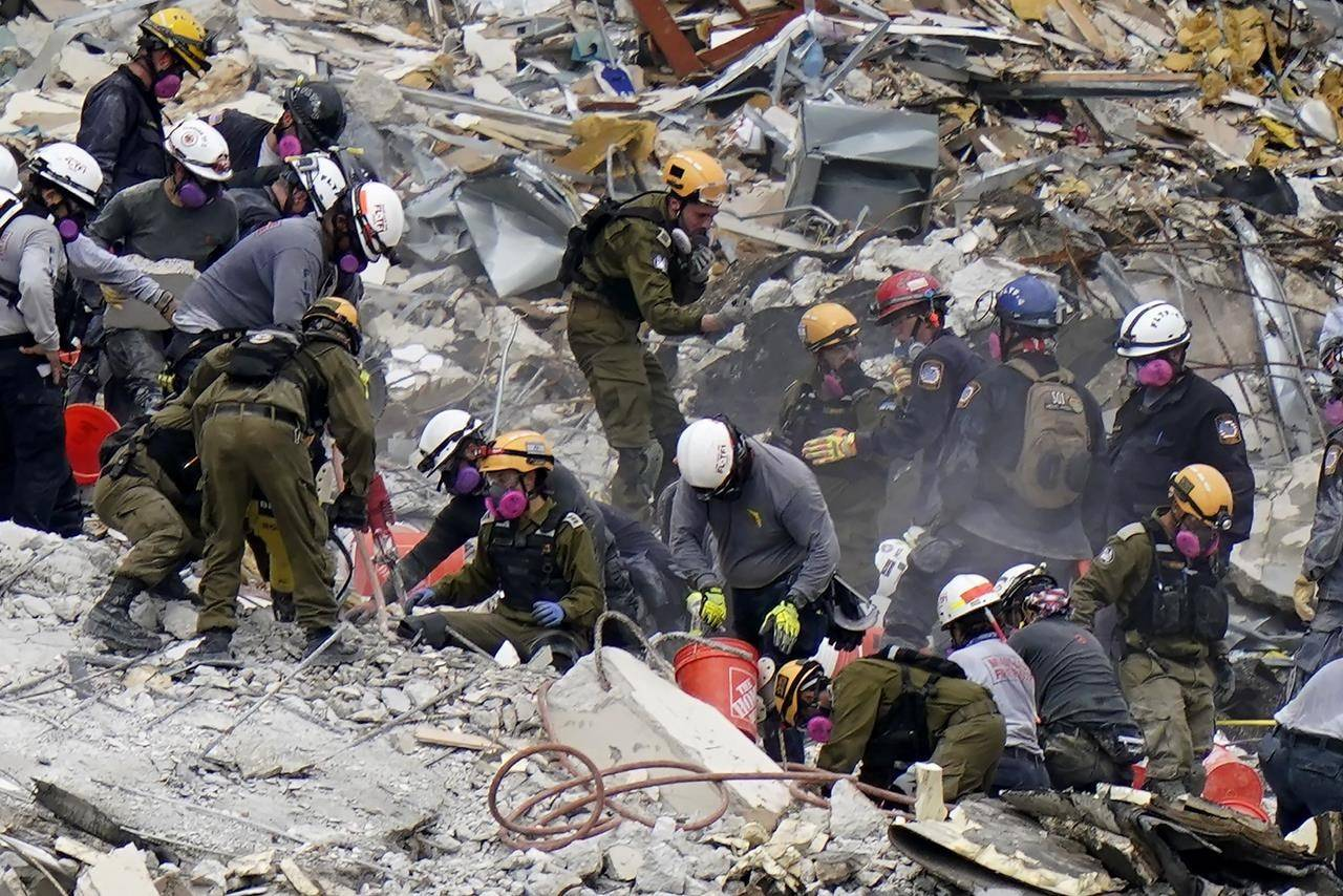 """FILE - Crews from the United States and Israel work in the rubble Champlain Towers South condo, Tuesday, June 29, 2021, in Surfside, Fla. The Israeli search and rescue team that arrived in South Florida shortly after the Champlain Towers South collapsed last month is heading home after an emotional sendoff in Surfside. The team planned to leave Florida on Sunday, July 11. During a brief Saturday evening ceremony, Miami-Dade Mayor Daniella Levine Cava thanked the battalion for their """"unrelenting dedication."""" (AP Photo/Lynne Sladky, File)"""