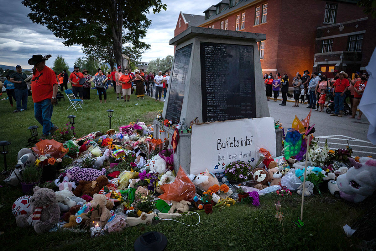FILE – People sing and drum at a memorial outside the former Kamloops Indian Residential School to honour the 215 children whose remains have been discovered buried near the facility, in Kamloops, B.C., on Monday, May 31, 2021. THE CANADIAN PRESS/Darryl Dyck