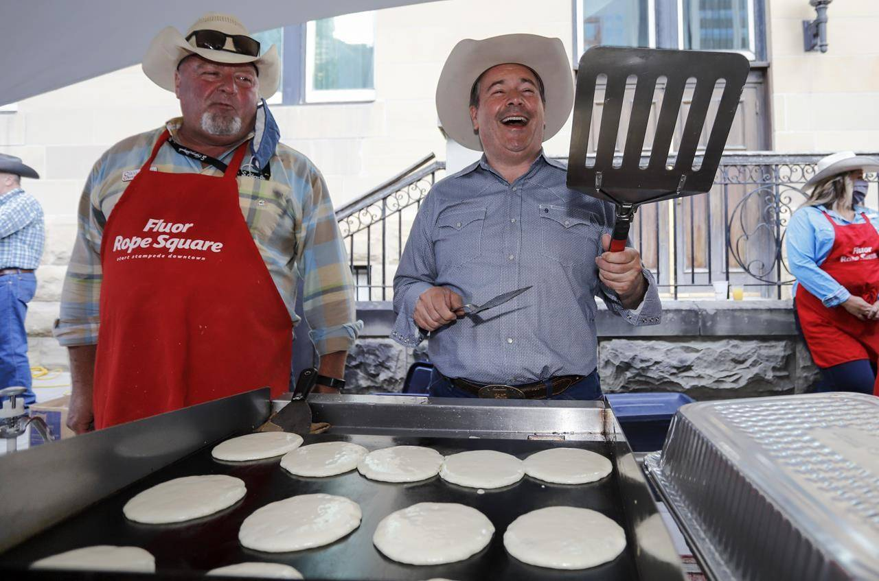 Alberta Premier Jason Kenney, right, laughs as he is handed an oversized spatula whole flipping pancakes at the Premier's annual Stampede breakfast in Calgary, Alta., Monday, July 12, 2021.THE CANADIAN PRESS/Jeff McIntosh
