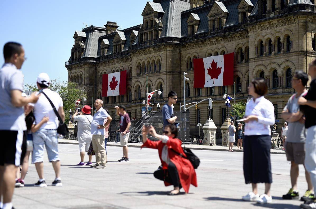 Canadian flags are seen on the Office of the Prime Minister and Privy Council as tourists take photos on Parliament Hill before Canada Day, in Ottawa on June 27, 2019. THE CANADIAN PRESS/Justin Tang