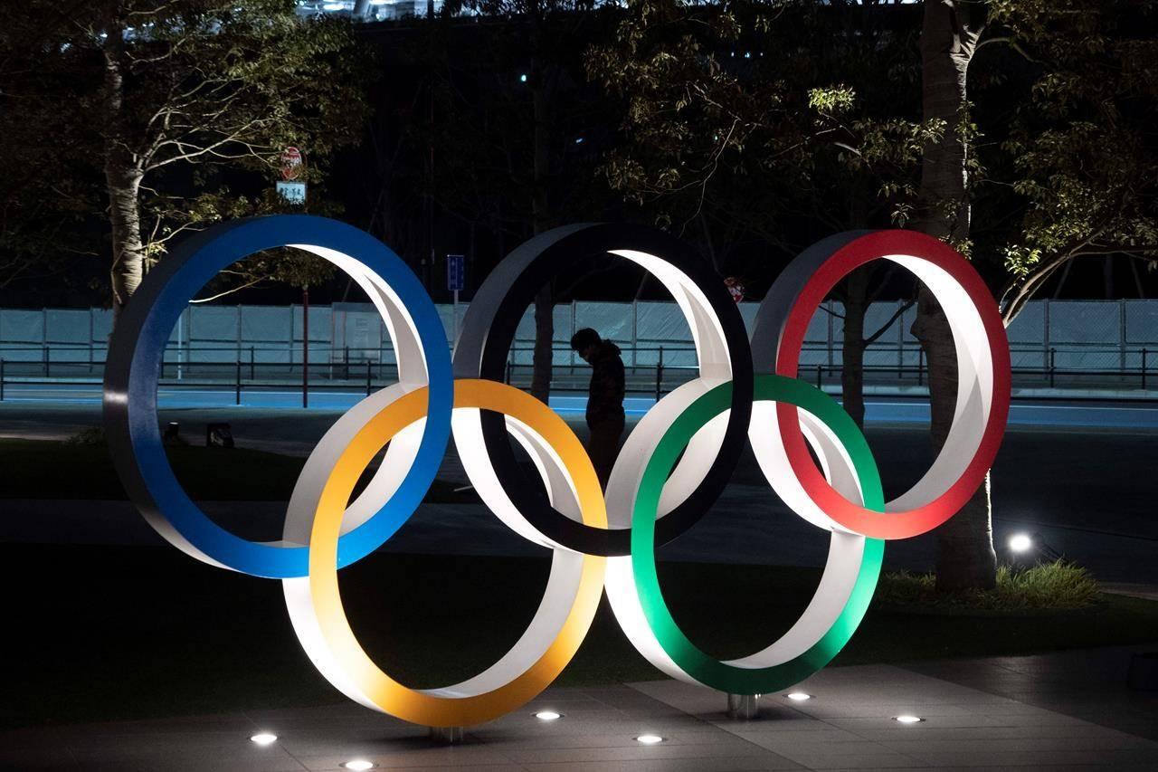 FILE - In this March 24, 2020, file photo, a man is seen through the Olympic rings installed near the National Stadium in Tokyo. (AP Photo/Jae C. Hong, File)
