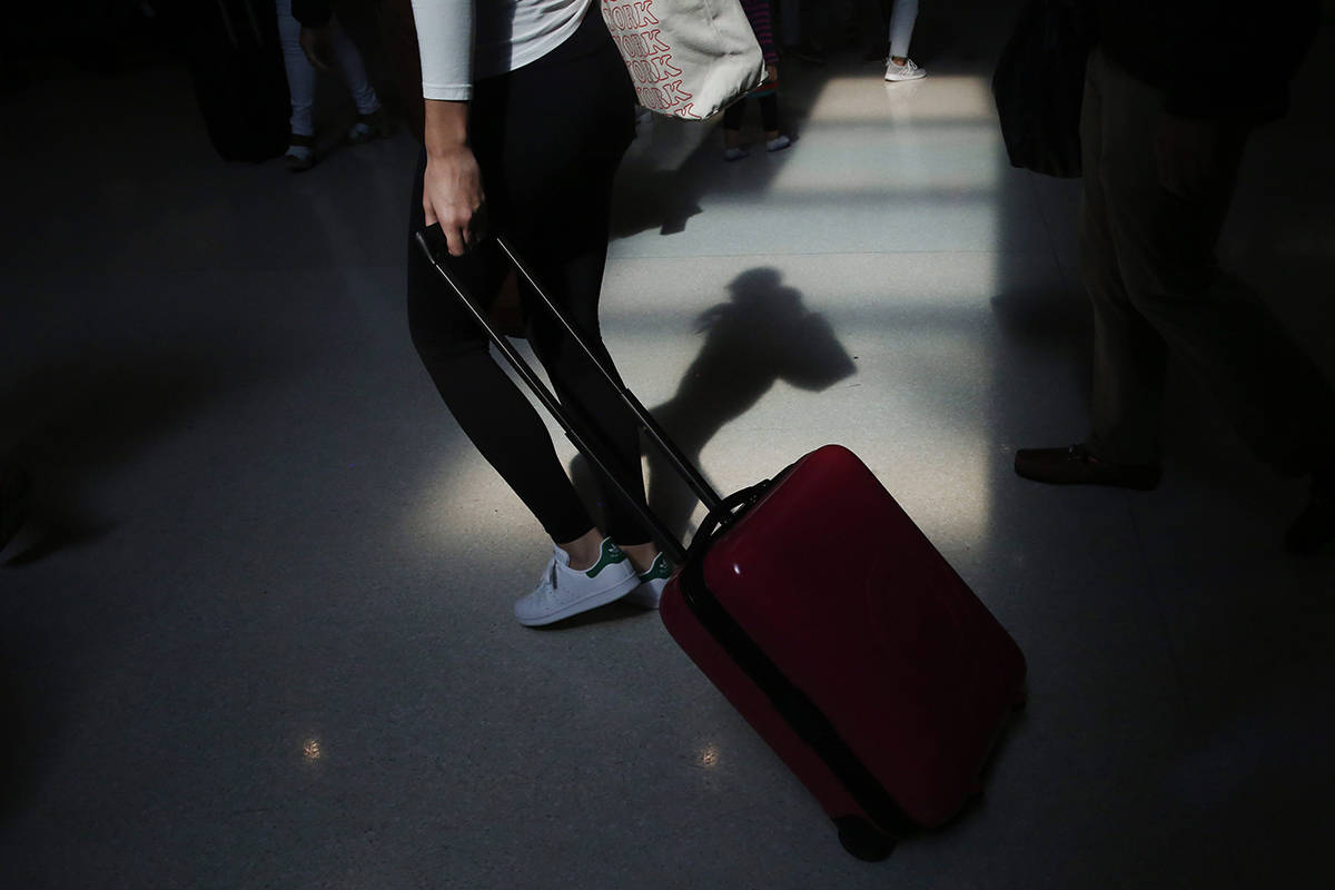 FILE - In this Nov. 27, 2019, file photo a traveler walks through the terminal at the Fort Lauderdale-Hollywood International Airport in Fort Lauderdale, Fla. (AP Photo/Brynn Anderson, File)