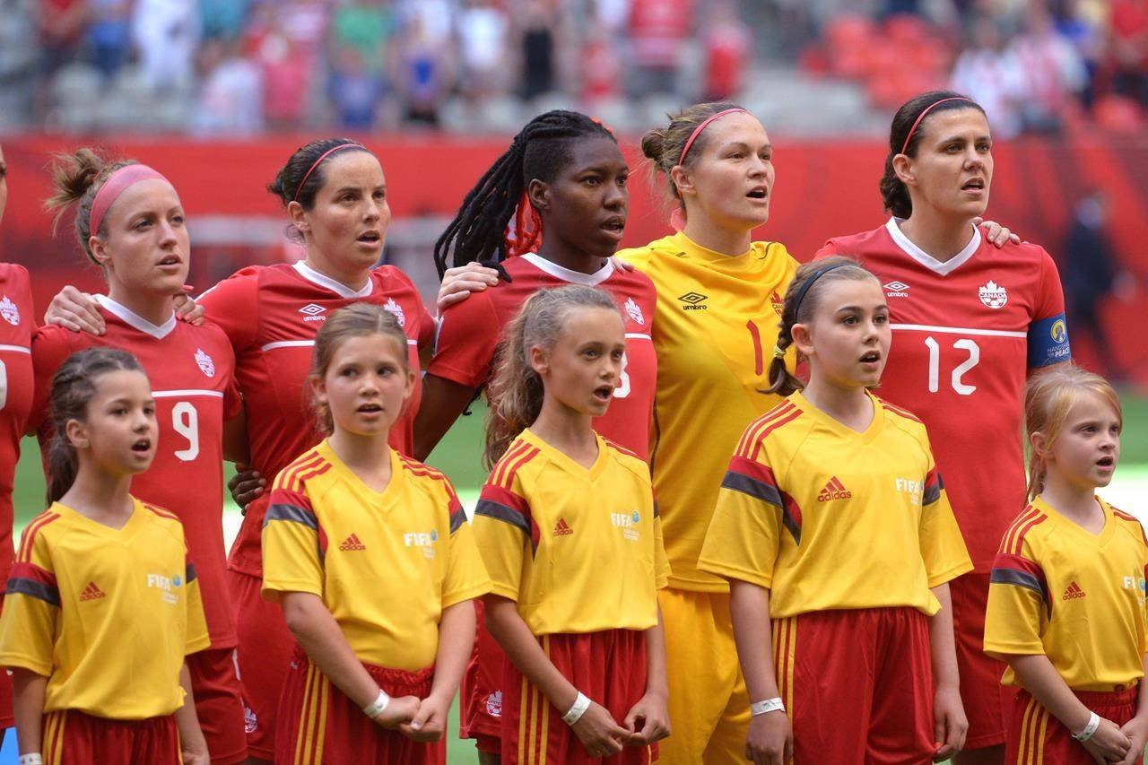 Children sing the national anthem with members of team Canada before the first half of the FIFA Women's World Cup round of 16 soccer action in Vancouver on Sunday, June 21, 2015. Canada's soccer fields, tennis courts and swimming pools are reopening after the pandemic, but a new study finds that many girls across the country may not go back to the sports they loved. THE CANADIAN PRESS/Jonathan Hayward