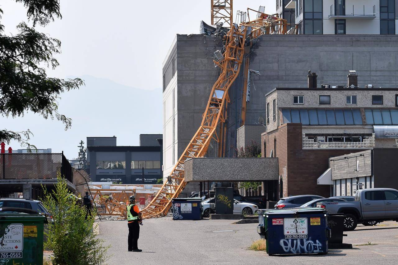 A worker looks on as a police officer investigates a collapsed crane resting on the building it damaged in Kelowna, B.C., Monday, July 12, 2021. THE CANADIAN PRESS/Alistair Waters