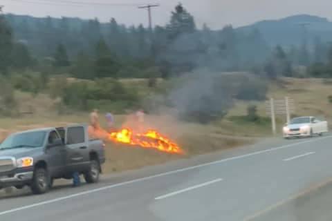 Two Okanagan Restoration Service employees snuffed a small blaze burning along Highway 97A in Spallumcheen Monday, July 12, 2021. (Okanagan Restoration Services Ltd. - Facebook)