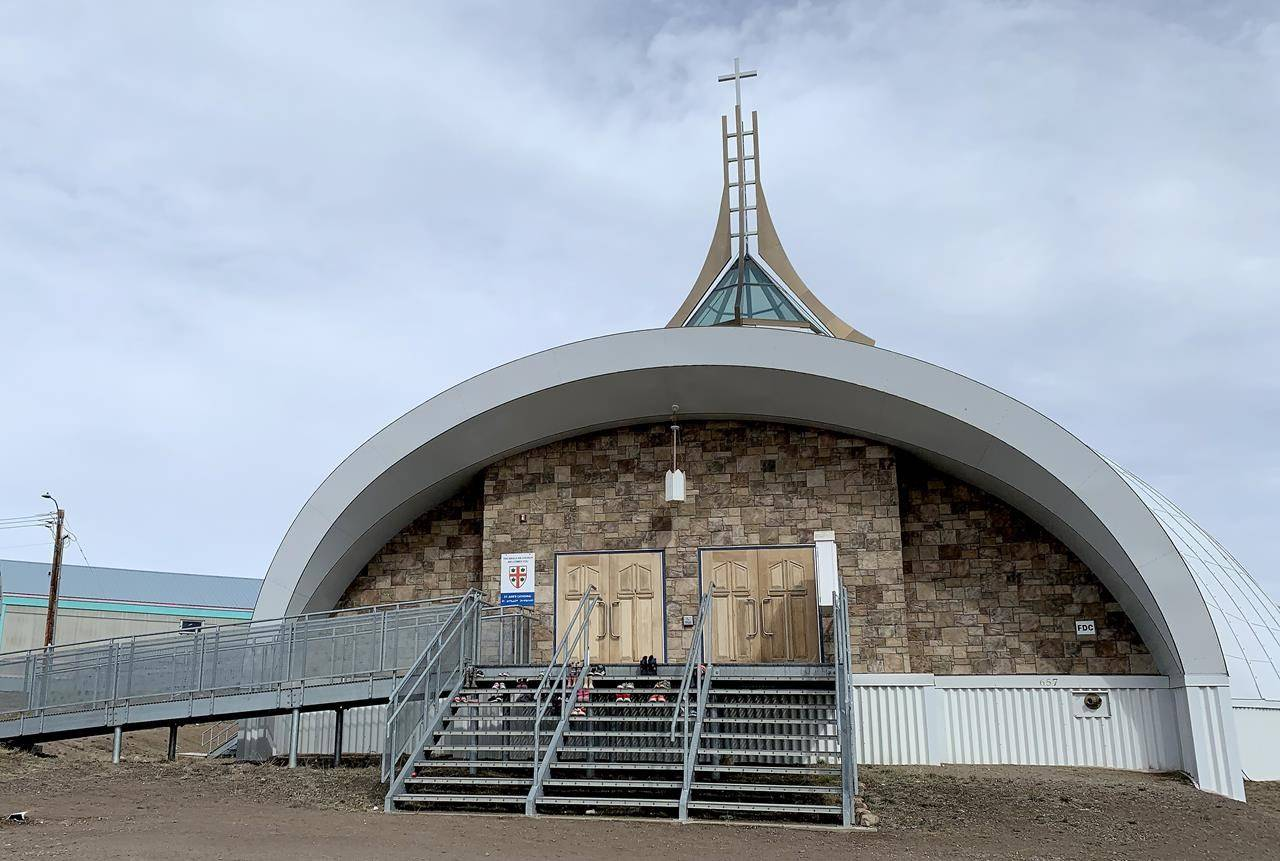 A few dozen children's shoes have been placed on the steps of St. Jude's Anglican Cathedral in Iqaluit, Friday, June 25, 2021. The mayor of Iqaluit says he will no longer bring forward a motion to make the city's churches to pay taxes on land use. THE CANADIAN PRESS/Emma Tranter
