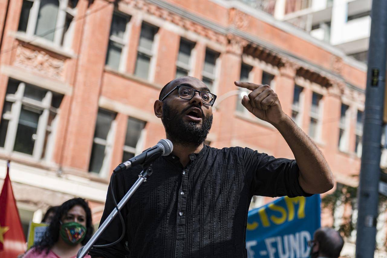 Syed Hussan, Executive Director of Migrant Workers Alliance, speaks to demonstrators during an action in support of migrant worker rights in front of the Immigration and Refugee Board of Canada, in Toronto, on Sunday, Aug., 23, 2020. THE CANADIAN PRESS/Christopher Katsarov