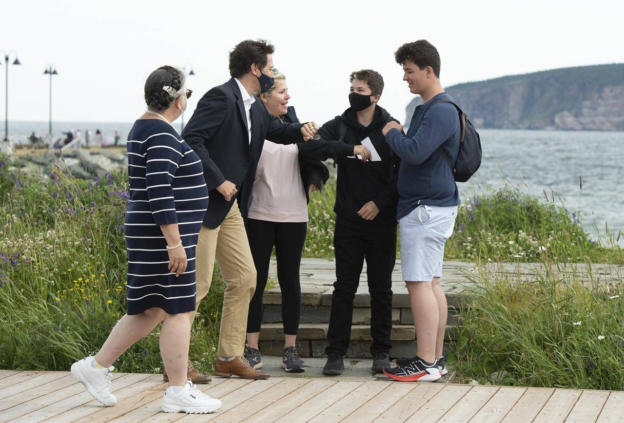 Prime Minister Justin Trudeau, second left, greets tourists as he takes a stroll on the boardwalk near the Percé Rock with Minister of National Revenue Diane Lebouthillier, left, following a meeting on Wednesday, July 14, 2021 in Percé, Que. THE CANADIAN PRESS/Jacques Boissinot