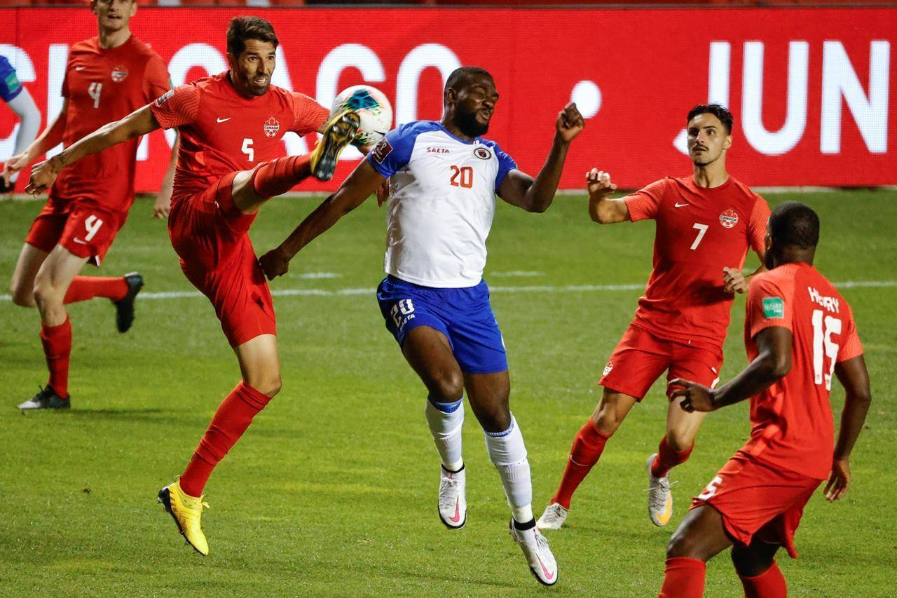 Canada's Steven Vitoria (5) kicks the ball next to Haiti's Frantzdy Pierrot (20) during the second half of a World Cup qualifying soccer match Tuesday, June 15, 2021, in Bridgeview, Ill. THE CANADIAN PRESS/AP-Kamil Krzaczynski