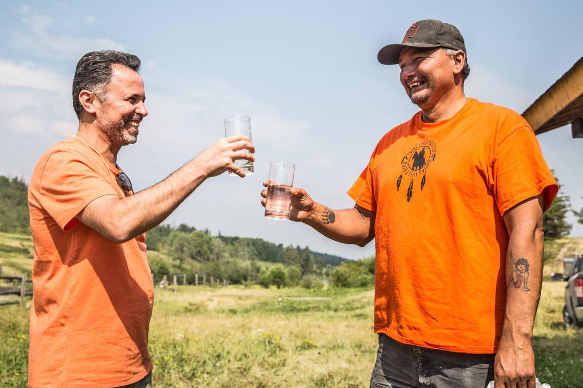 UBC professor Madjid Mohseni and Kluskus water operator Tony Baptiste enjoy a glass of water. (UBC Submitted Photo)