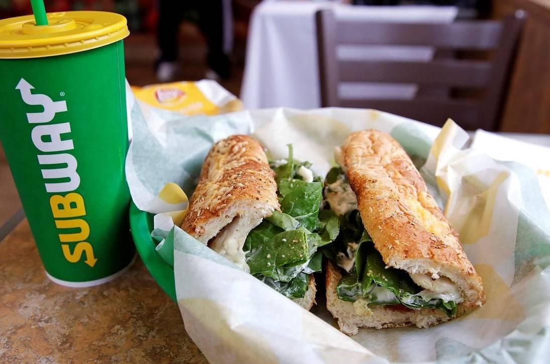 In this Friday, Feb. 23, 2018 file photo, the Subway logo is seen on a soft drink cup next to a sandwich at a restaurant in Londonderry, N.H.. THE CANADIAN PRESS/AP -Charles Krupa