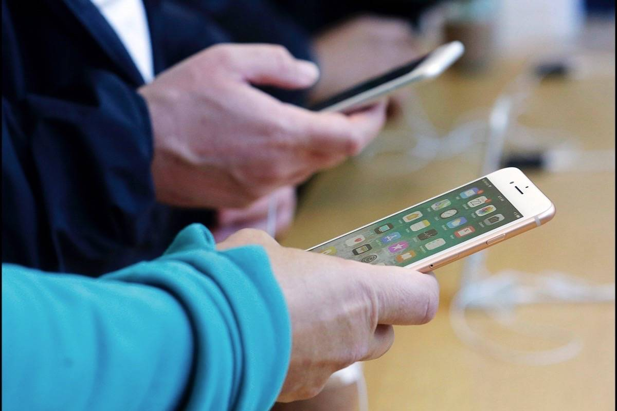 FILE - In this Sept. 22, 2017, file photo, customers look at iPhone 8 and iPhone 8 Plus phones at an Apple Store in San Francisco. (AP Photo/Jeff Chiu)