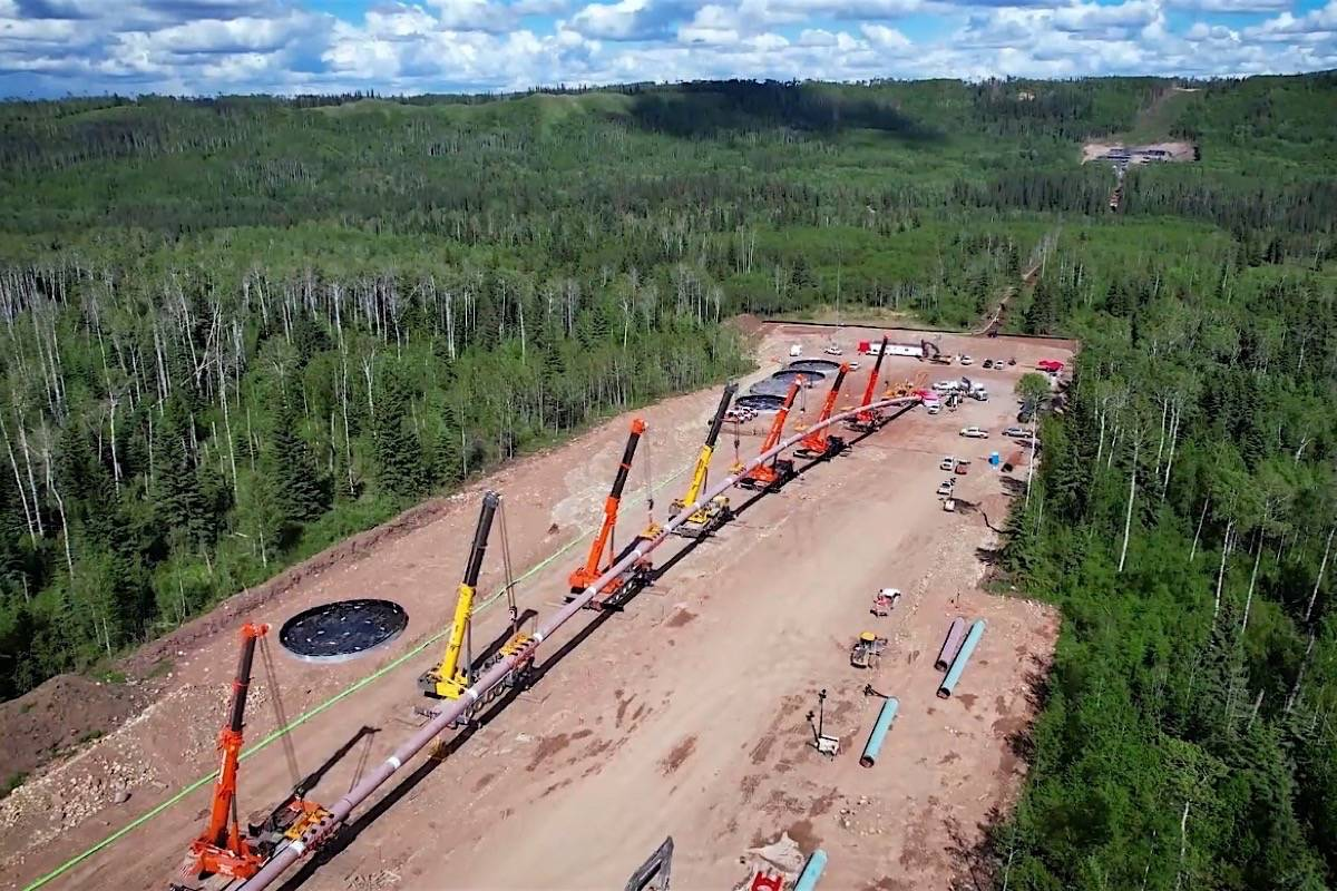 Cranes guide sections of Coastal Gaslink pipeline into a 1.3 km tunnel under the Murray River in northeast B.C., June 2021. (Coastal Gaslink video)