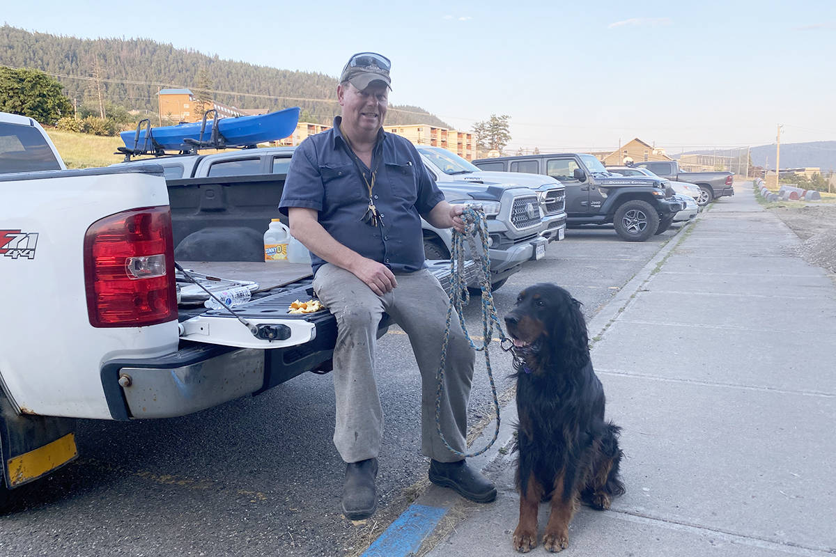 Lone Butte resident Brad Mason waits outside the ESS Centre in Williams Lake Wednesday evening, July 14 with his dog Archie as his wife Victoria registers them as evacuees. (Angie Mindus photo - Williams Lake Tribune)