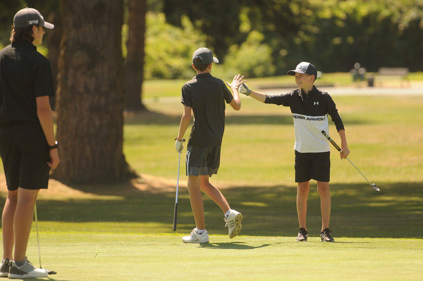Owen Hopfner (right) congratulates Nathan Devisser (both of Chilliwack) on his successful putt on the third green at Chilliwack Golf Club during the final round of the 2021 Optimist Fred Wellsby Junior Divot golf tournament on Thursday, July 15, 2021. (Jenna Hauck/ Chilliwack Progress)