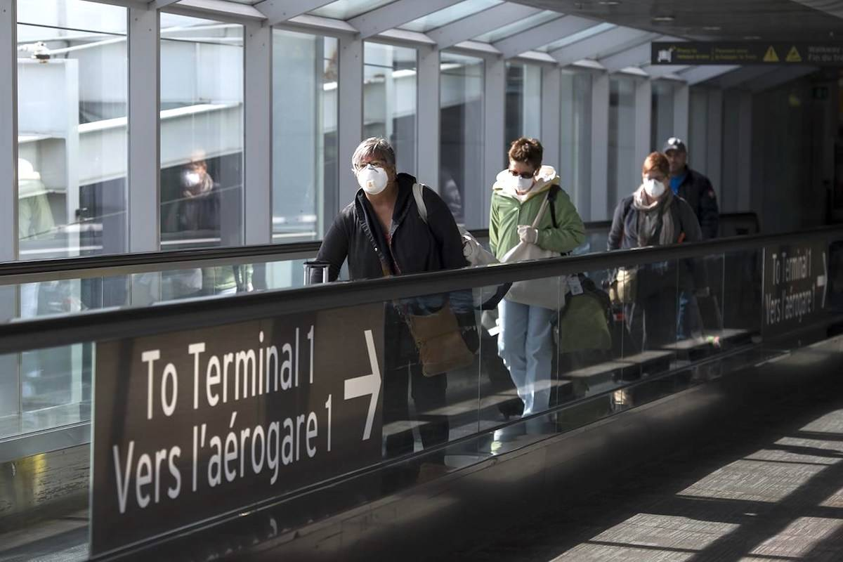 People leave the airport after arriving at Pearson International Airport in Toronto on Monday, March 16, 2020. THE CANADIAN PRESS/Nathan Denette