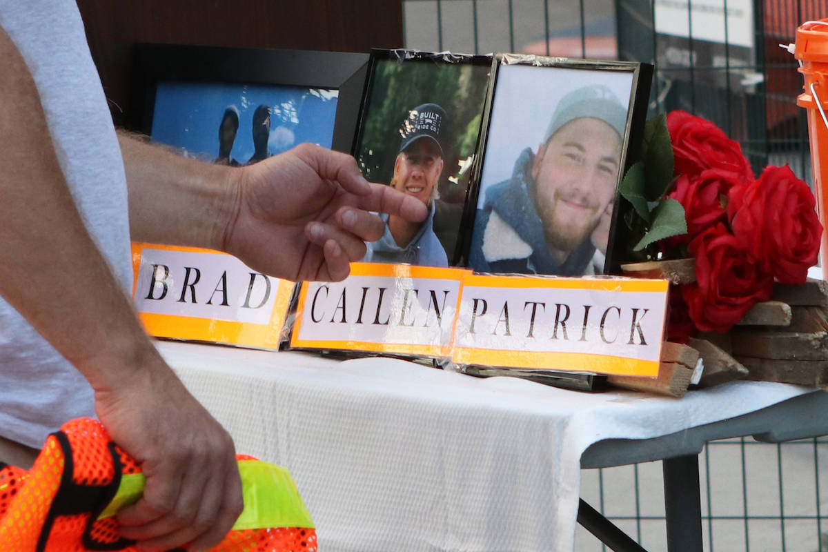 Chris Vilness, the father of 23-year-old Cailen Vilness, brushes a photo of his son at the vigil site. (Aaron Hemens/Capital News)