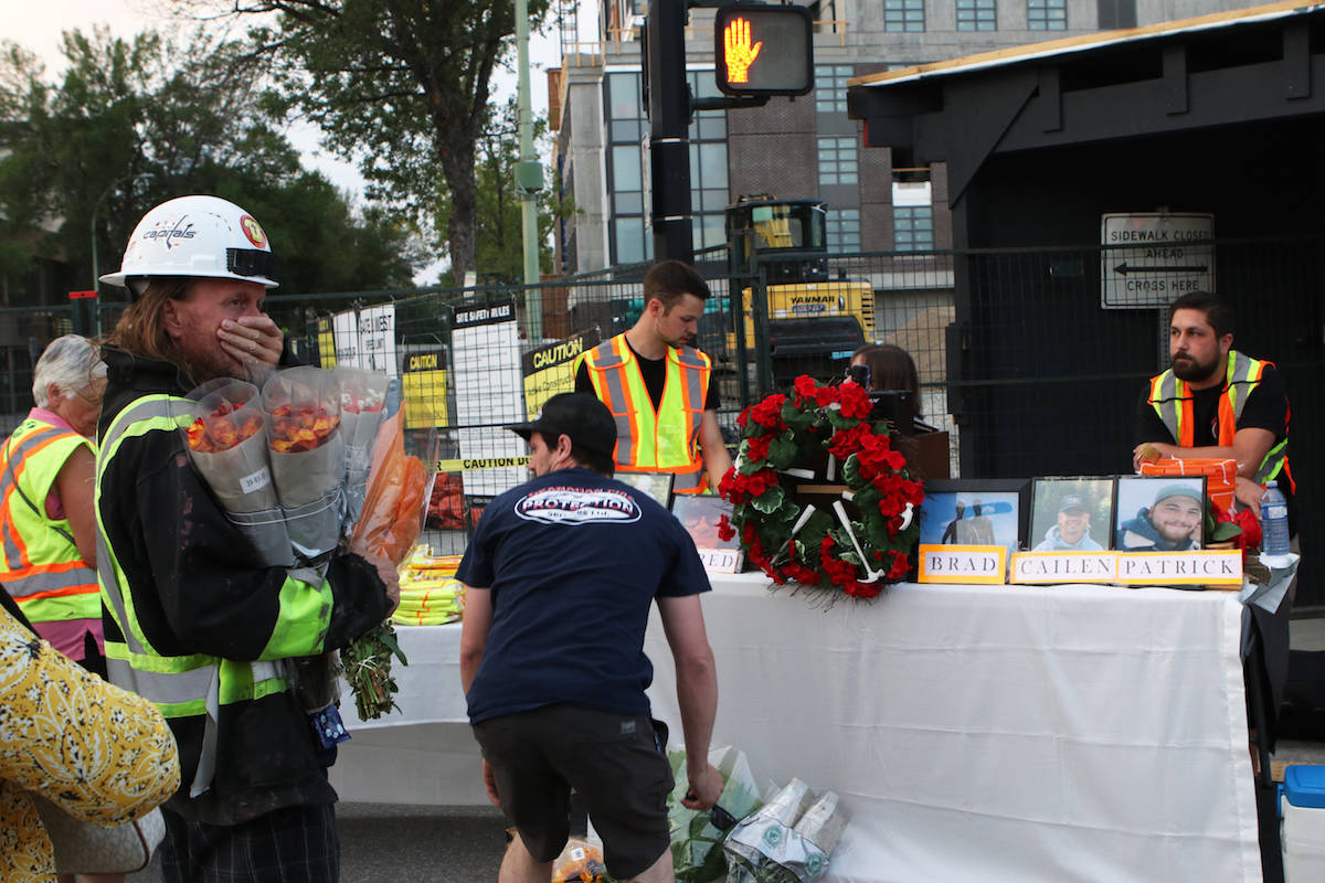 People leave down flowers at the vigil site. (Aaron Hemens/Capital News)