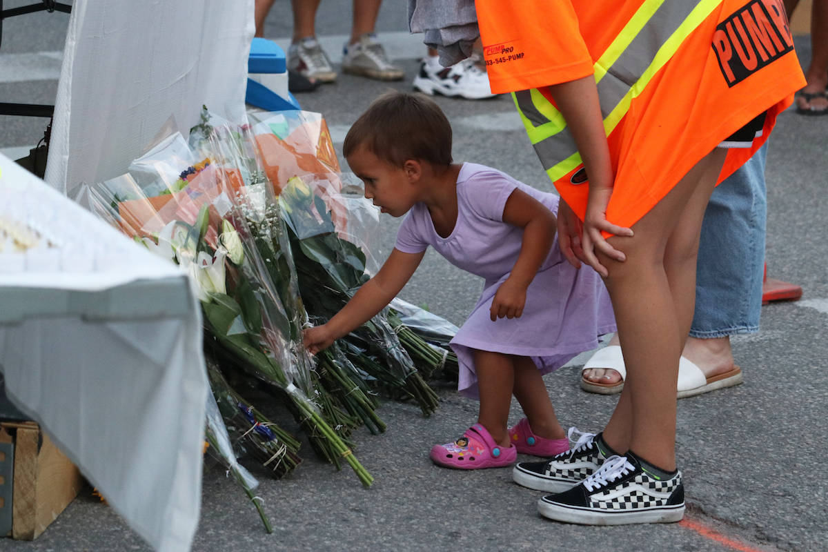 A youth leaves a bouquet of flowers at the vigil site. (Aaron Hemens/Capital News)