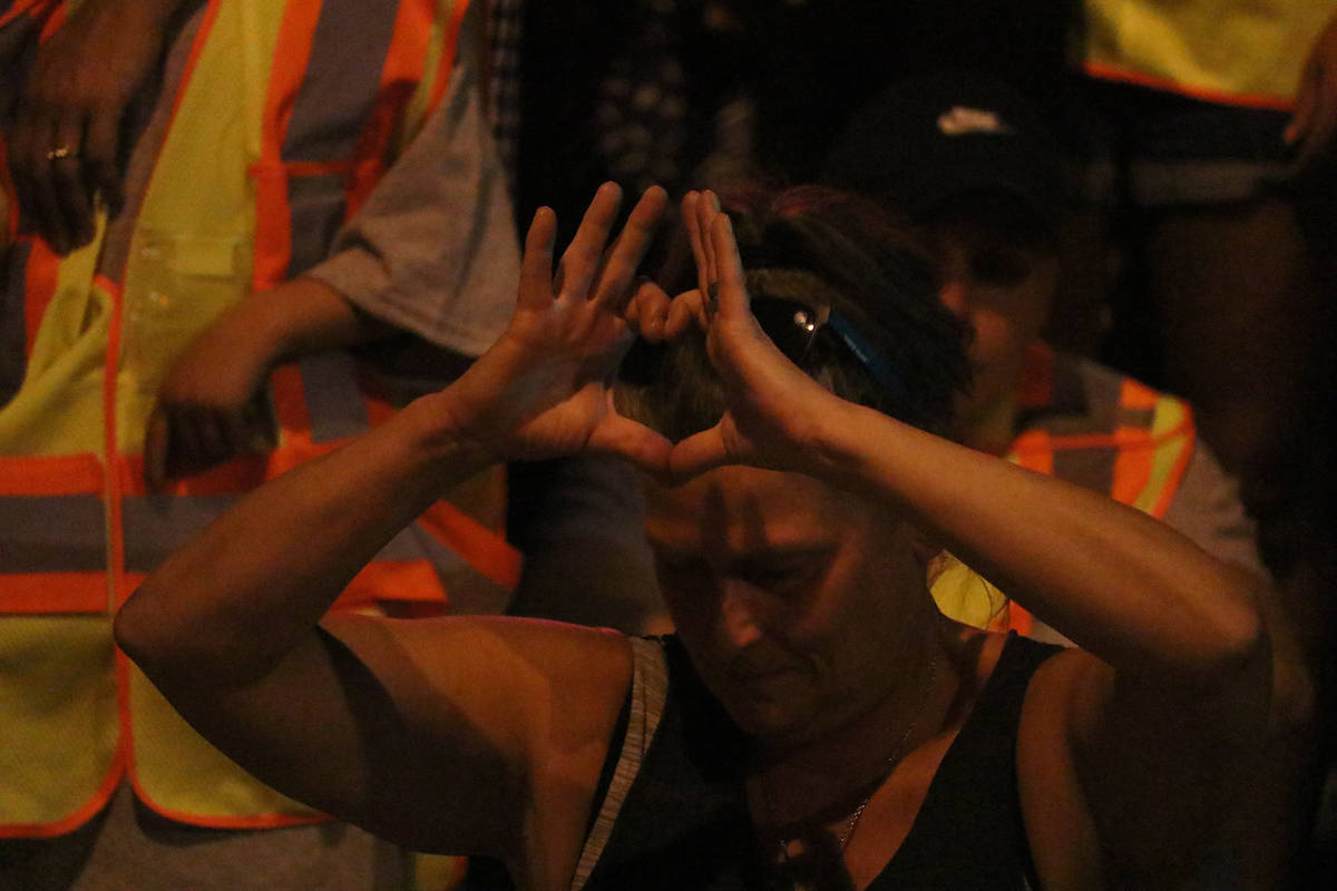 An attendant makes a heart shape with their hands. (Aaron Hemens/Capital News)
