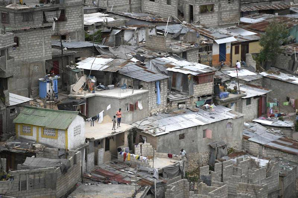 Neighbors stand on a roof in Port-au-Prince, Haiti, Monday, July 12, 2021. (AP Photo/Matias Delacroix)