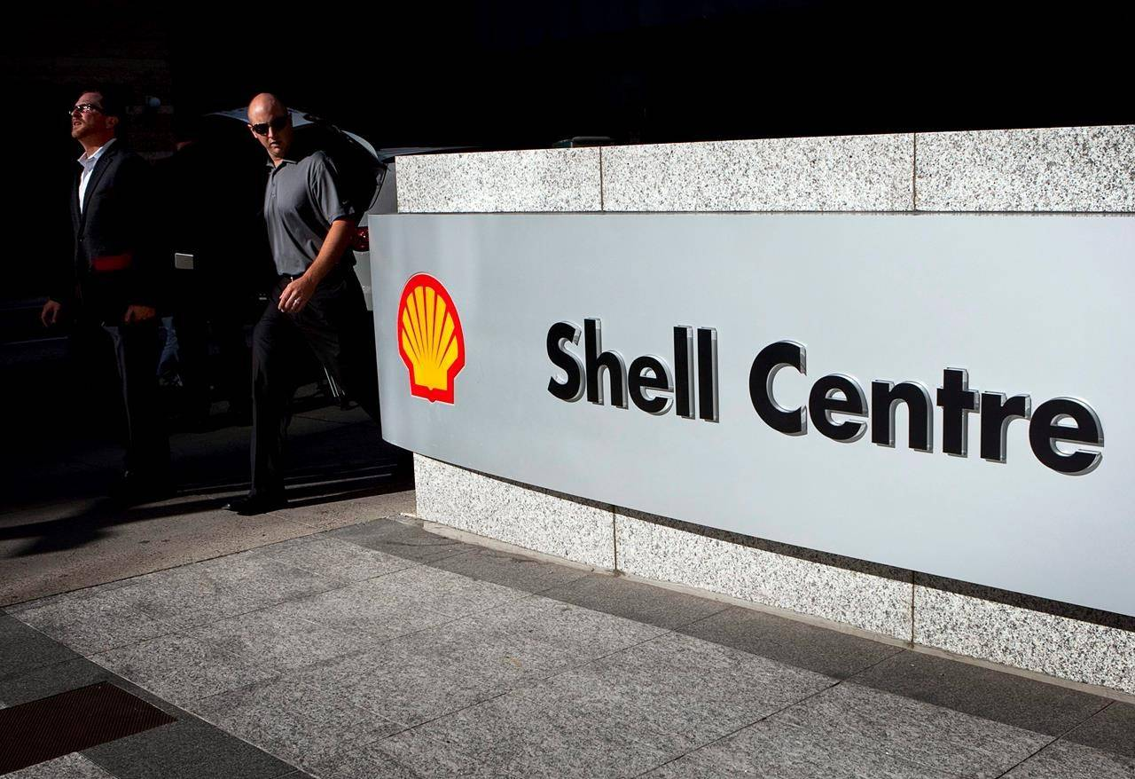 Pedestrians walk past Shell Canada's headquarters before a news conference in Calgary on August 26, 2010. THE CANADIAN PRESS/Jeff McIntosh
