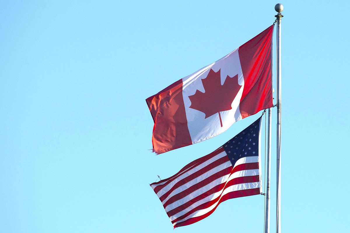 Canadian and U.S. flags fly above the Peace Arch at the Canada-USA border in Surrey, B.C. Canada has announced U.S. residents can visit without border testing starting Aug. 9 if they are fully vaccinated. THE CANADIAN PRESS