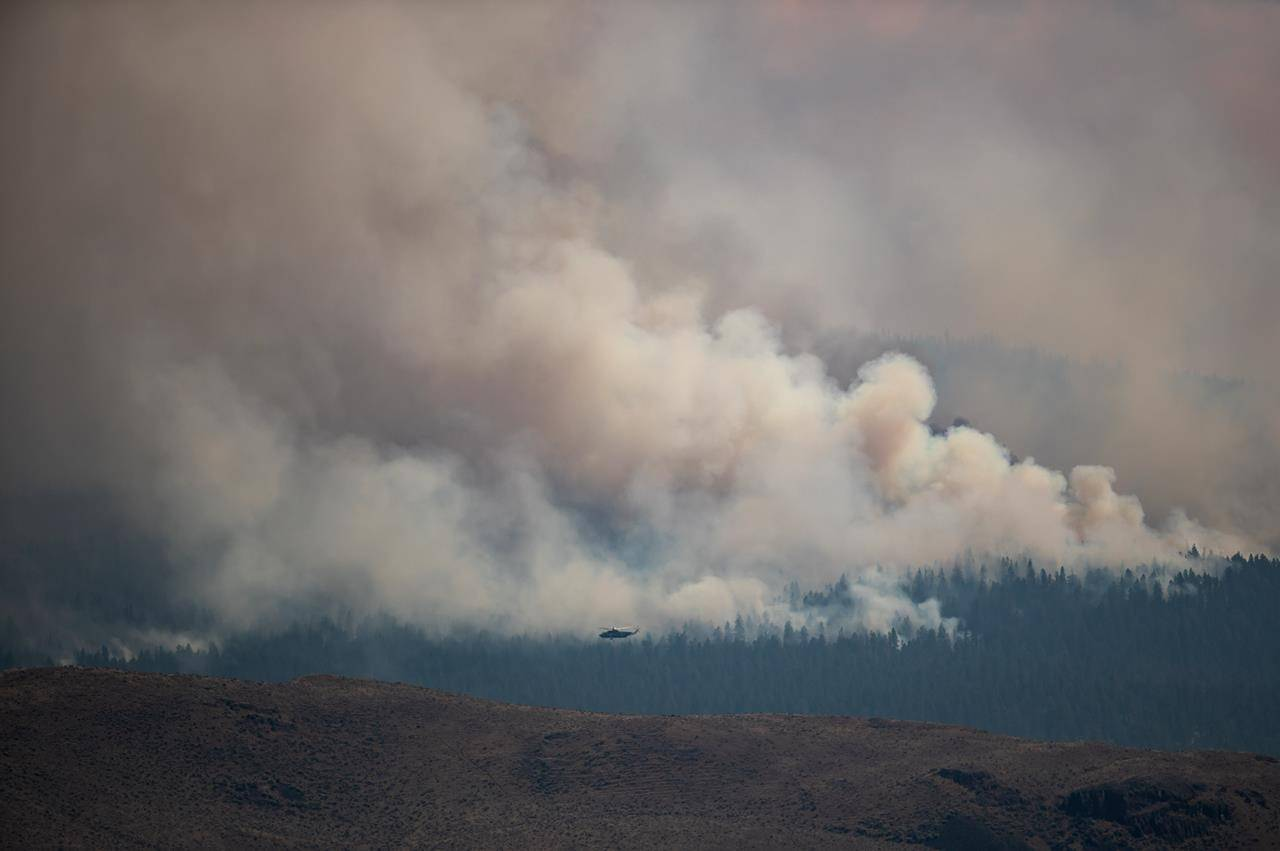 A helicopter flies past the Tremont Creek wildfire burning on the mountains above Ashcroft, B.C., on Friday, July 16, 2021. THE CANADIAN PRESS/Darryl Dyck