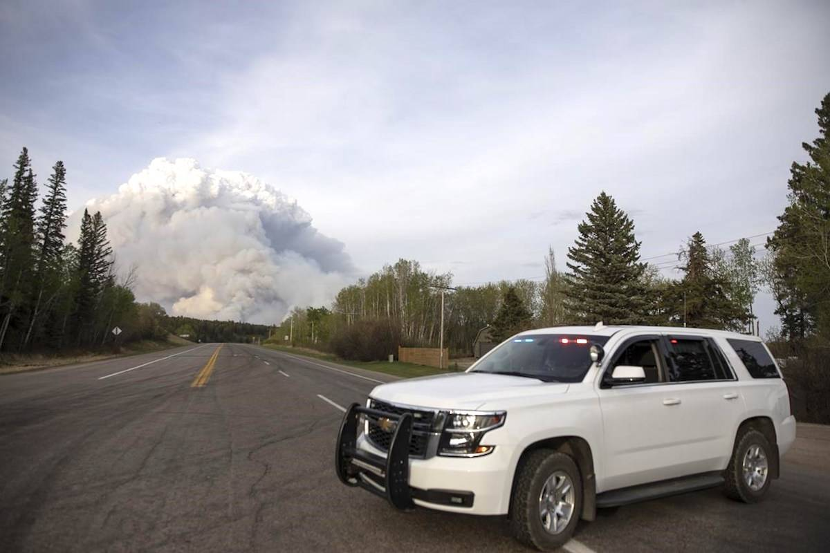 A plume of smoke rise from a forest fire burning northeast of the city in Prince Albert, Sask., Monday, May 17, 2021. (The Canadian Press/Kayle Neis)