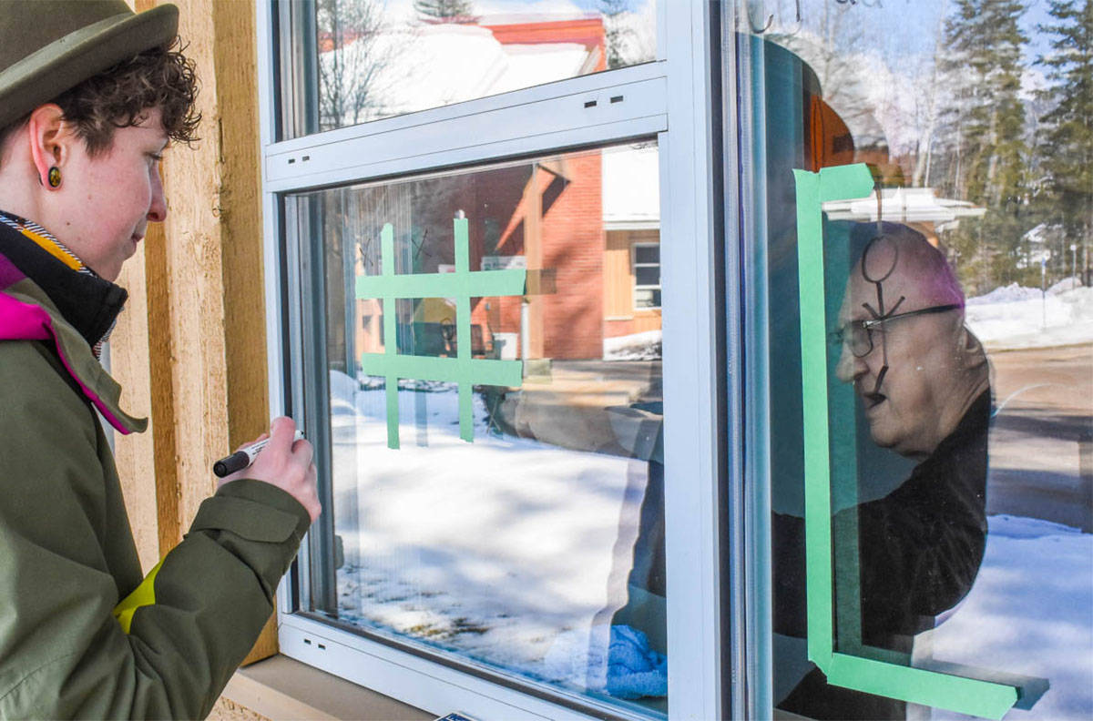 Theresa Hamilton plays tic tac toe on a window with a senior in Mt. Cartier Court as the pandemic limited in-person visitors into senior care homes. Visit restrictions have been eased effective July 19, 2021. (Liam Harrap/Revelstoke Review)
