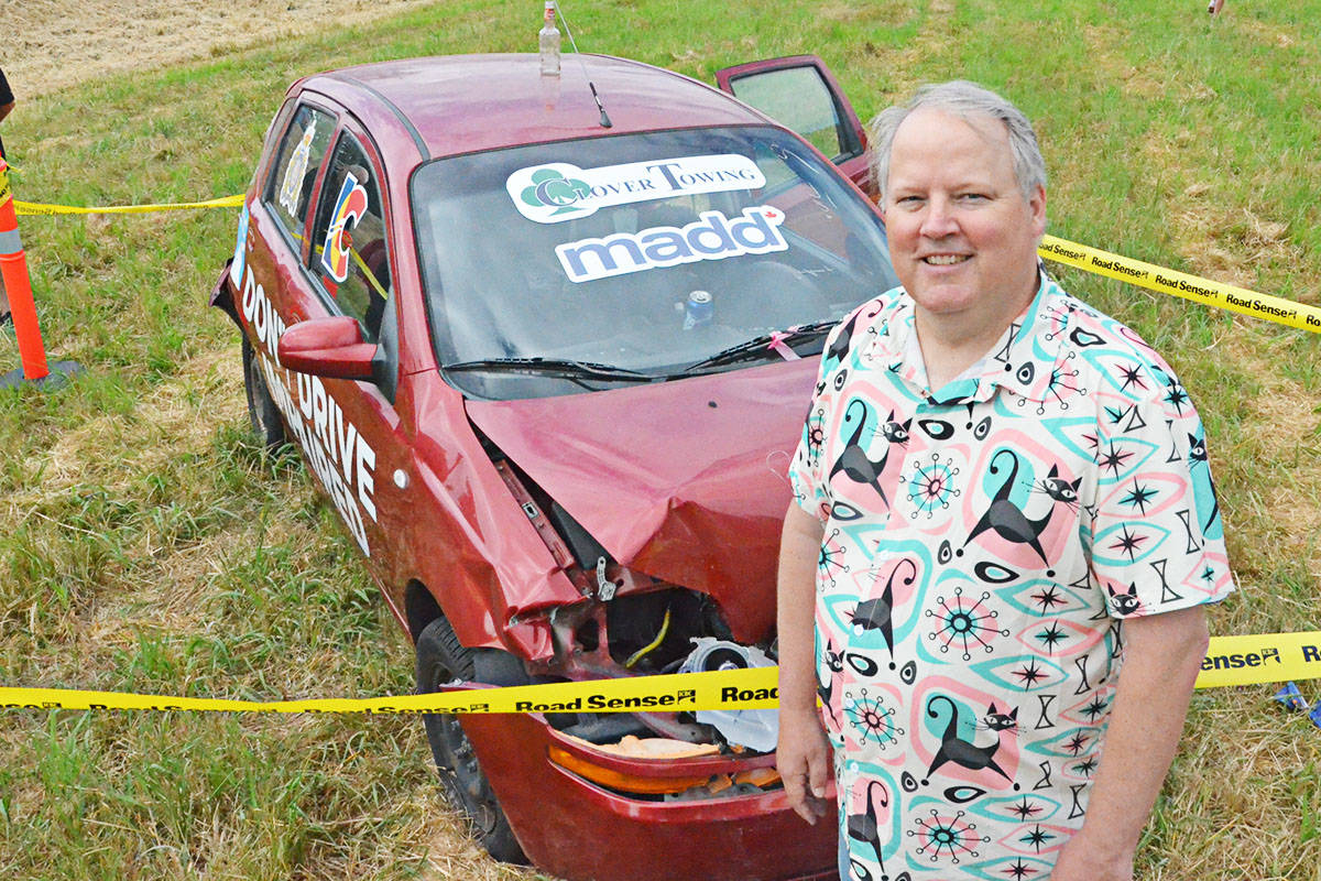 Charlie Grahn, treasurer of the Vancouver chapter of Mothers Against Drunk Driving, with the crashed car that will warn local drivers in Langley this month. (Matthew Claxton/Langley Advance Times)