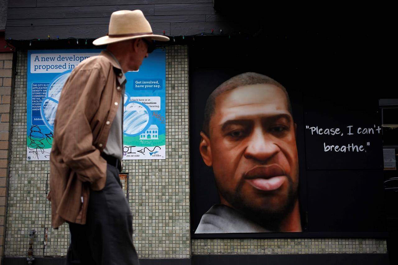 People walk by a mural of George Floyd, airbrushed by artist Paul Archer on Fort St. in Victoria, B.C., on Wednesday, June 10, 2020. A new report shows many companies that signed a pledge to help end anti-Black racism still don't have diversity, equity and inclusion plans a year later. THE CANADIAN PRESS/Chad Hipolito