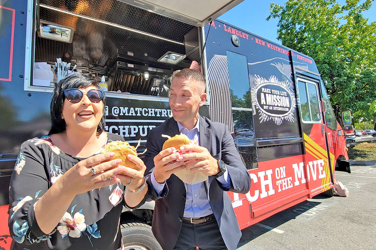 Langley City Mayor Val van den Broek and Gateway Casinos & Entertainment Ltd. Vice-president of Food and Beverage Todd Pollock tuck into some burgers at the debut of the company's new food truck in Langley City at the Cascades Casino Resort on Wednesday, July 21. (Dan Ferguson/Langley Advance Times)