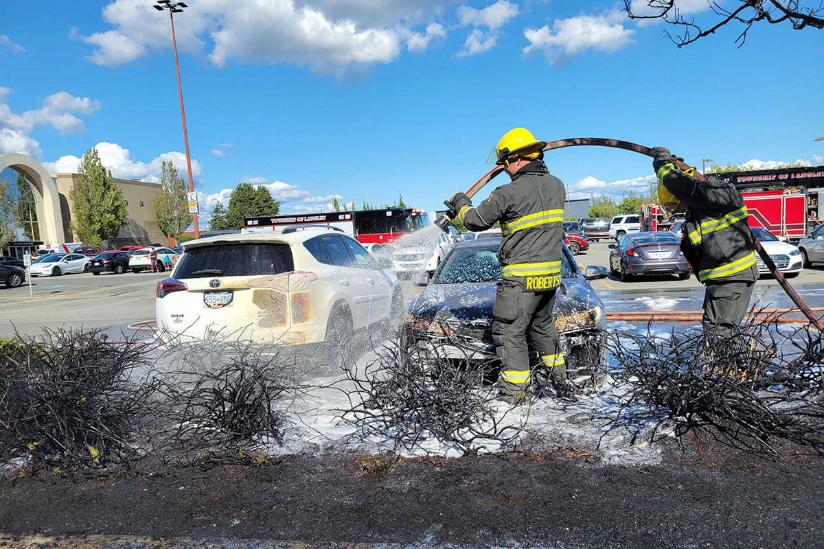Firefighters soak a scorched stretch of trees in the parking lot of the Willowbrook Mall on Wednesday afternoon. The parking lot fire caused the evacuation of the mall. (Dan Ferguson/Langley Advance Times)