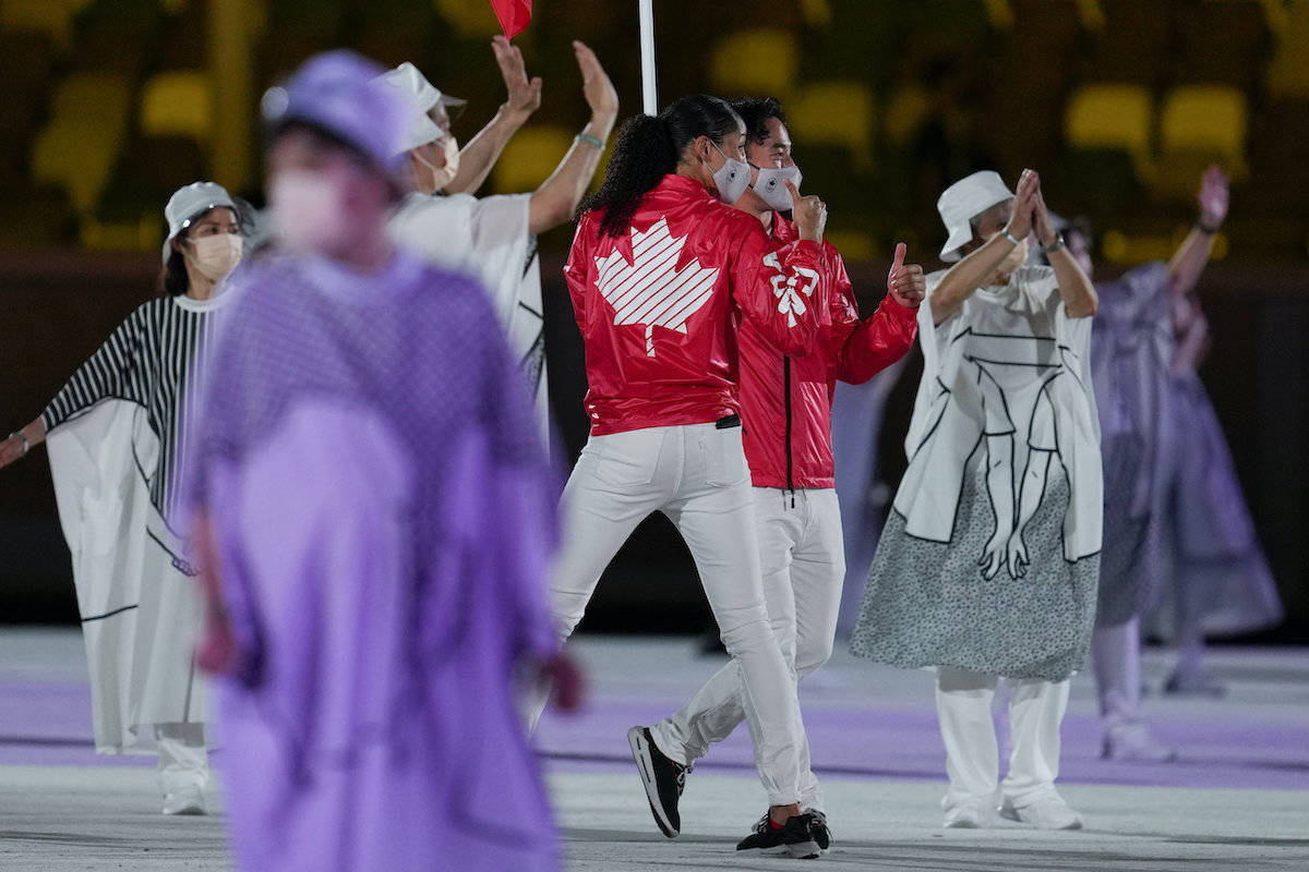 Miranda Ayim and Nathan Hirayama, of Canada, carry their country's flag during the opening ceremony in the Olympic Stadium at the 2020 Summer Olympics, Friday, July 23, 2021, in Tokyo, Japan. (AP Photo/Natacha Pisarenko)